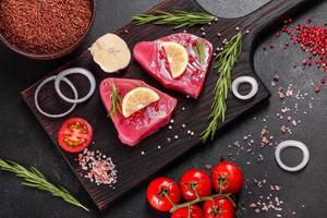 Fresh tuna fillet steaks with spices and herbs on a black background photo