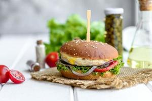 Delicious fresh homemade burger on a wooden table photo