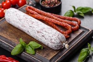 Español salami salchicha seca sobre un fondo de hormigón oscuro foto