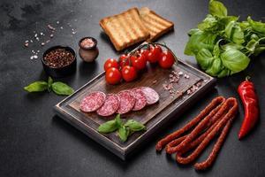 Spanish dried sausage salami on a dark concrete background photo