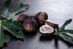 higos maduros frescos sobre un fondo de hormigón oscuro. cosechando higos foto