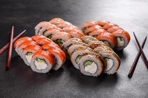 Rollos de sushi hermosos y deliciosos frescos sobre un fondo oscuro foto