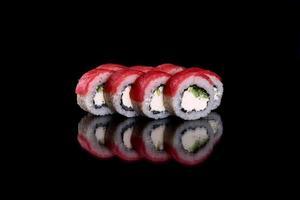 Fresh delicious beautiful sushi rolls on a dark background photo