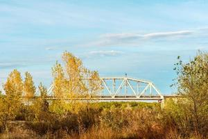 A metal railway bridge connecting two river banks photo