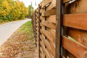 An old fence of wooden planks around a plot of land photo