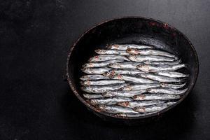 Varios pescados de anchoas saladas sobre una mesa de hormigón oscuro foto