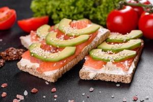 Delicious fresh sandwich with red fish, butter, bread and avocado photo
