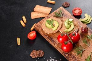 Tasty fresh sandwich with liver paste, avocado pieces and a arugula photo