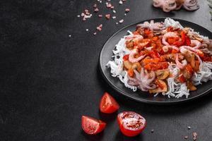sabrosos fideos de arroz con tomate, pimiento rojo, champiñones y marisco foto