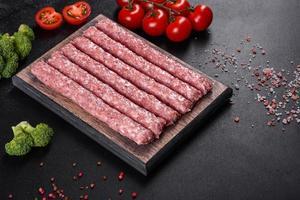 Salchichas de cerdo cruda fresca con especias sobre una tabla de cortar de madera foto