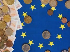 Euro notes and coins, European Union, over flag photo