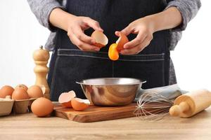 Woman hands to separate egg white and yolks with egg shells photo
