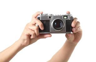 Mano sujetando una cámara vintage sobre fondo blanco. foto