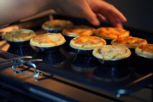 Mini pie from meat and mushrooms baking in industrial oven photo