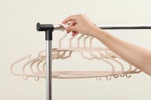 Women hand holding plastic hangers on rack photo