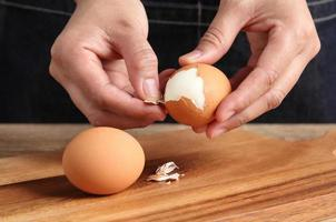 Chef peeling boiled egg on cutting board in kitchen photo
