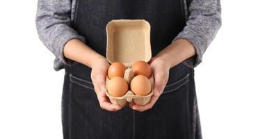Mujer sosteniendo huevos de gallina frescos en caja de cartón foto