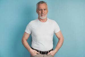 Senior, bearded man in a white T-shirt posing on a blue background photo