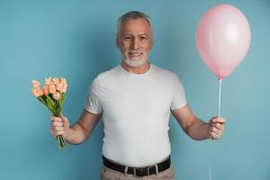 Gallant, senior man holds flowers and pink balloon in his hand photo