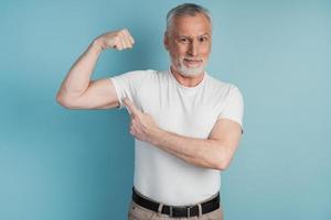 Senior hombre barbudo mostrando músculos vistiendo camiseta blanca pose foto