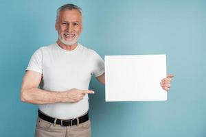 Smiling, pleasant, senior man holds a white piece of paper photo