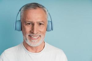 Close-up view, positive man in headphones smiling on blue background photo