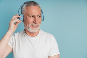 Attractive, smiling man in headphones posing on a blue background photo