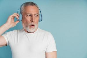 Surprised man in headphones posing on blue wall background, isolated photo