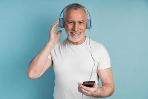 Positive, smiling senior man and beard wears headphones photo