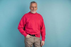 Handsome, mature man in a crimson pullover posing on a blue background photo