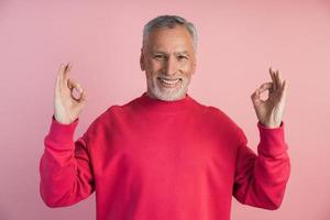 Smiling man meditating on a pink background photo