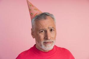 Sad, upset senior man in a festive hat on a pink background. photo