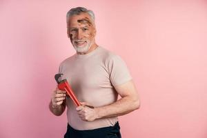Gray-haired male builder smiles in his hand holding a wrench photo