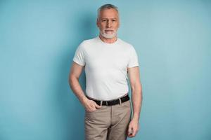 Senior man standing on a background of a blue wall photo