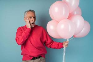 Surprised, the older man holds pink balloons in his hand photo