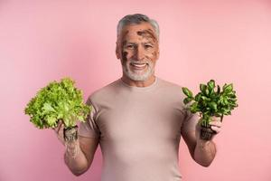 Older man, a farmer, is holding greens in his hands photo