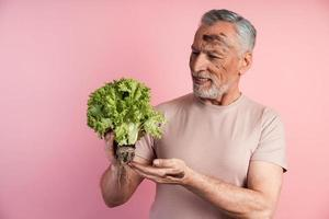 Handsome man is holding a handful of lettuce leaves photo