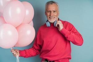 A smiling, older bearded man wears headphones photo