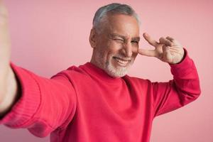 Positive man shows V sign, gesture of victory, peace photo