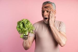 Shocked farmer holds a bunch of lettuce leaves in his hands photo