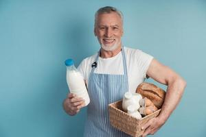 Senior, cute man holding a basket of groceries photo