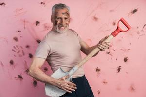 Funny, cheerful, elderly man holding a shovel as if holding a guitar photo