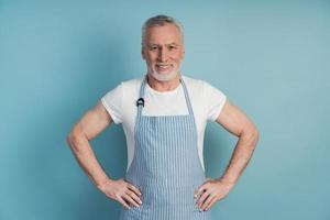 Older, elderly man with his hair and beard wears an apron photo