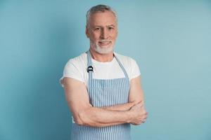 Attractive, elderly man in a blue apron posing on a blue background photo