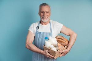 Smiling man with gray hair and beard holding a food basket photo