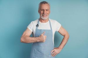 Joyful, positive retiree shows thumbs up, wears an apron photo