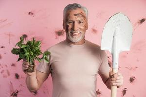 Smiling, attractive, older man holds grown greens photo
