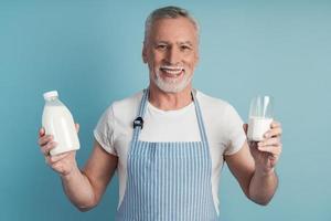 hombre sonriente sosteniendo un vaso de leche y una botella foto