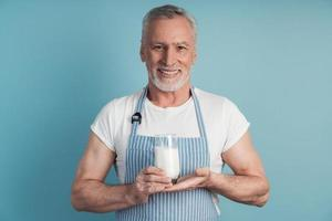 hombre sonriente sosteniendo un vaso de leche foto