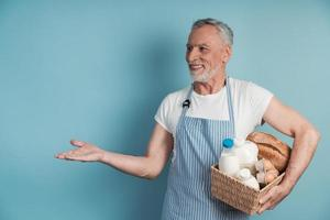 Positive man with gray hair and beard holding food basket photo